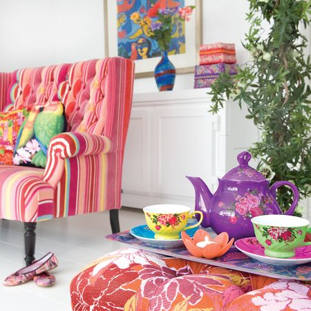 Pink patterned sofa with colourful vintage tea set