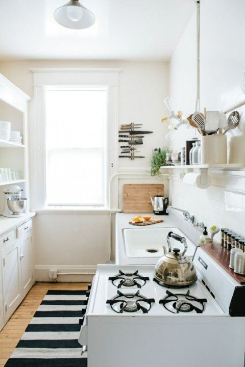 White kitchen with black and white rug and features - Photo found on thekitchn.com