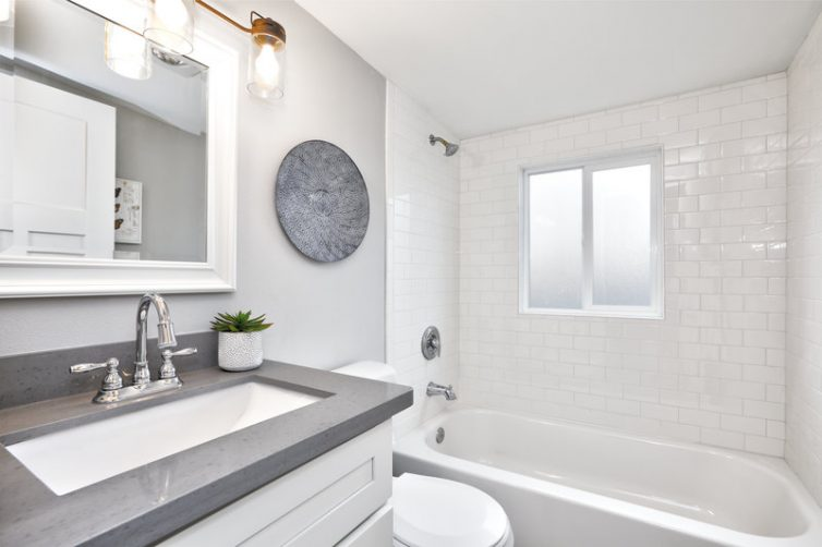 Modern bathroom interior with white vanity topped with grey countertop.