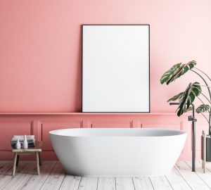 Interior of minimalistic bathroom with pink walls, wooden floor, white bathtub with vertical poster hanging above it and potted plant. 3d rendering mock up