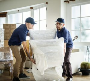Two Men Lifting Chair. Removal Company.