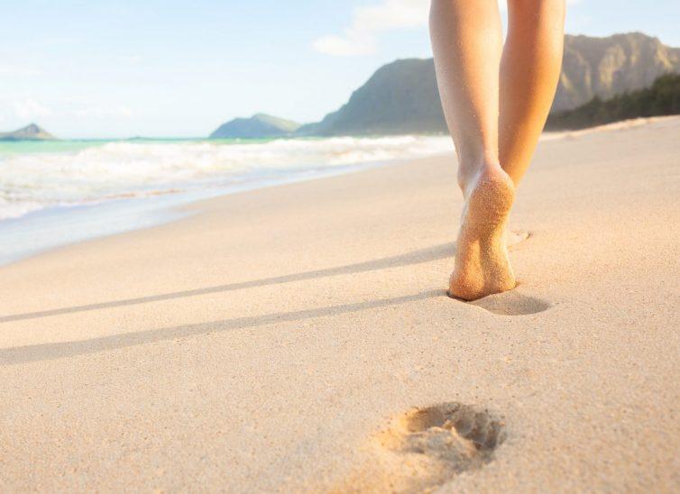 Woman walking on sandy beach leaving footprints in the sand.