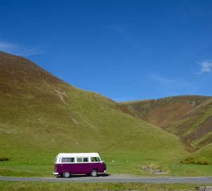 Purple VW camper van in the hills of Scotland