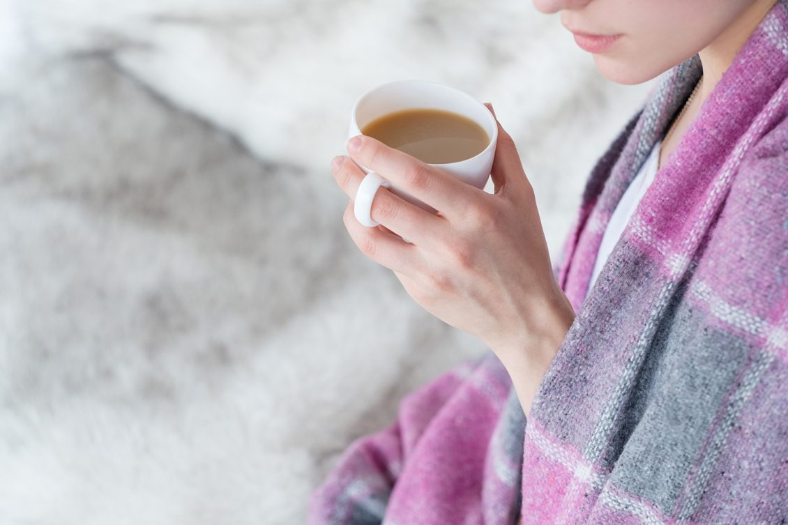 Women wrapped in blanket drinking hot drink