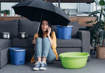 Women sat in loung with umbrella as ceiling leaking water