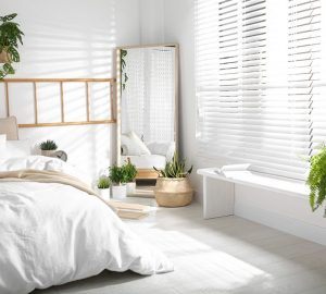 White decorated bedroom with large mirror and white wooden blinds