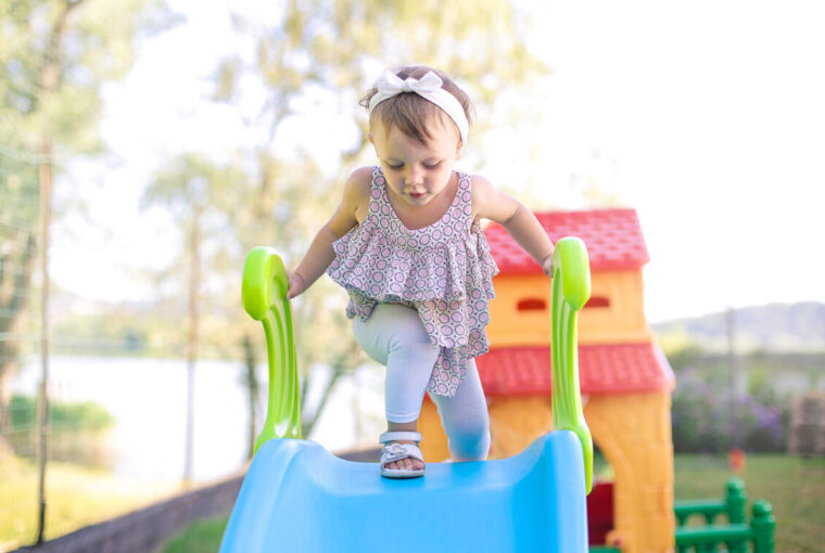 Young child playing on slide