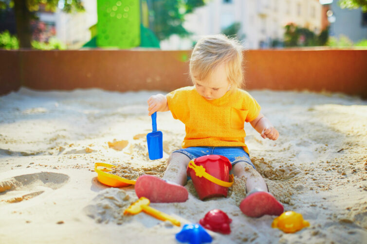 Young child playing in sandpit.