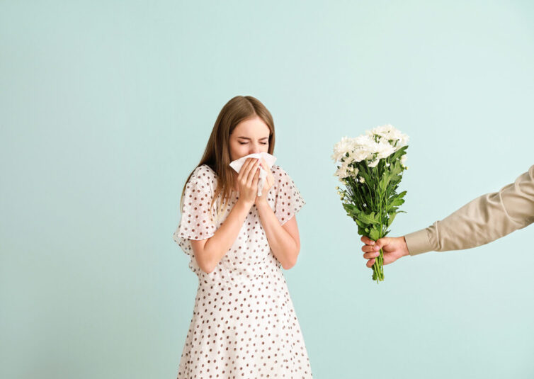 Women with allergies sneezing due to being given flowers