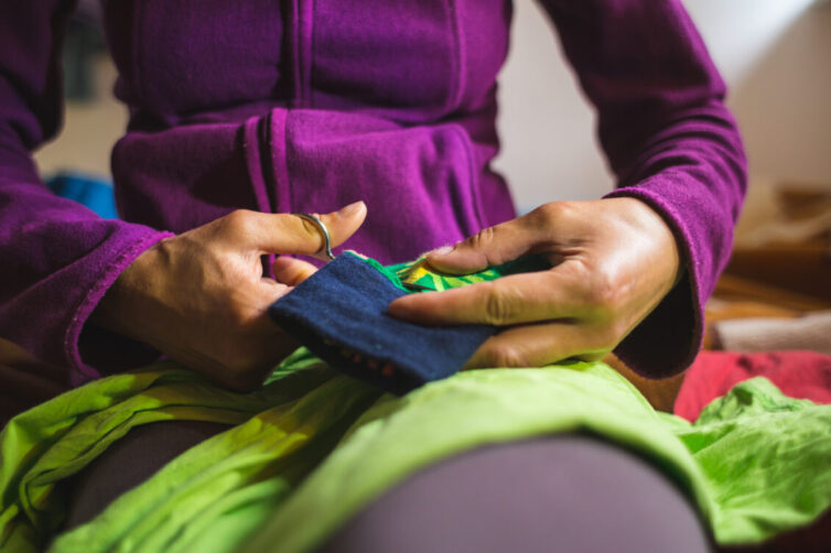 A woman sews a patch on torn clothes