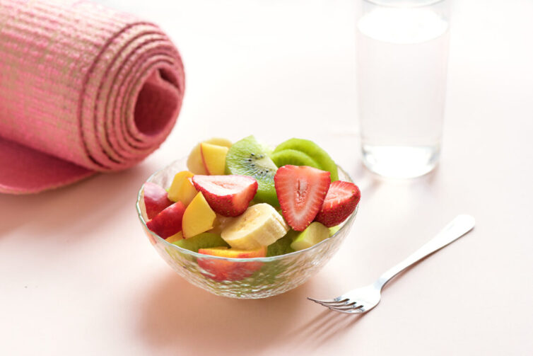 Bowl of fruit, yoga mat and glass of water