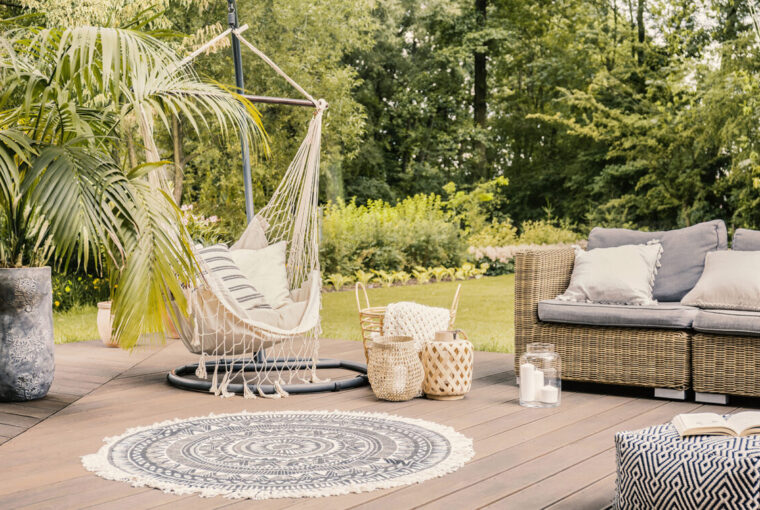 Hammock on patio with round rug and rattan sofa in the garden