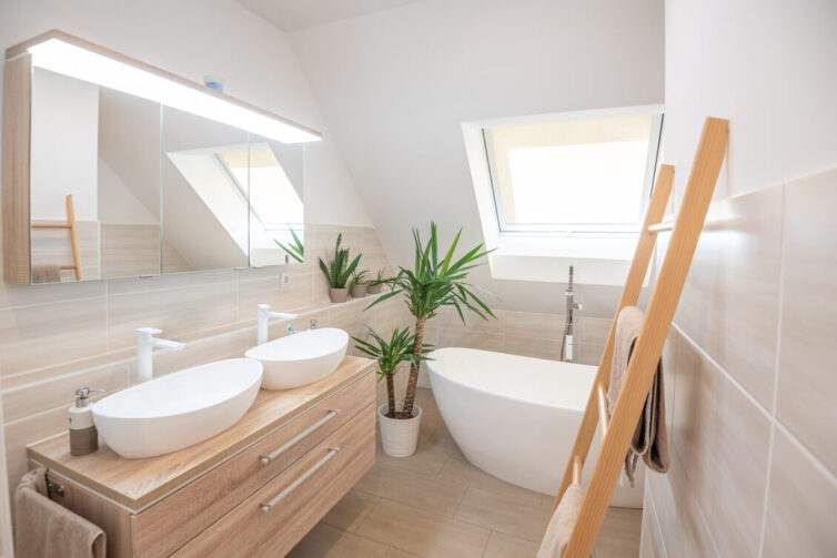 Bathroom with double sink, soft lighting and skylight