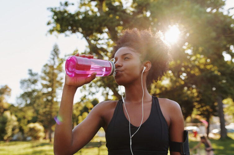 Fitness athlete young african american woman listening to music on earphones drinking water in a reusable water bottle after working out