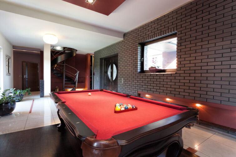 A big red pool table in a luxurious interior