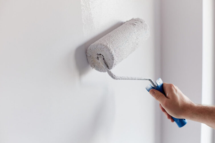 Painting wall with white paint on roller