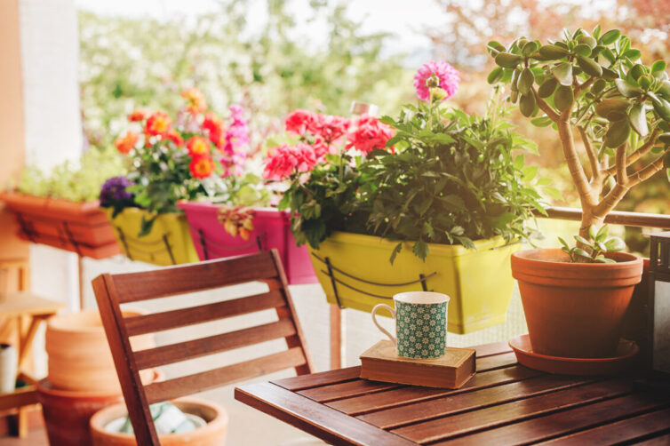 Balcony with wooden table and chairs and bright coloured planters full of plants
