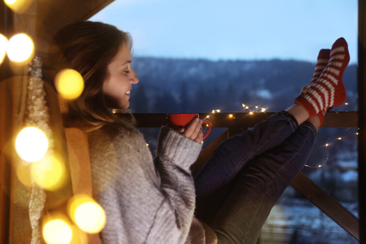 Women in jumper sat on balcony with hot drink and fairy lights