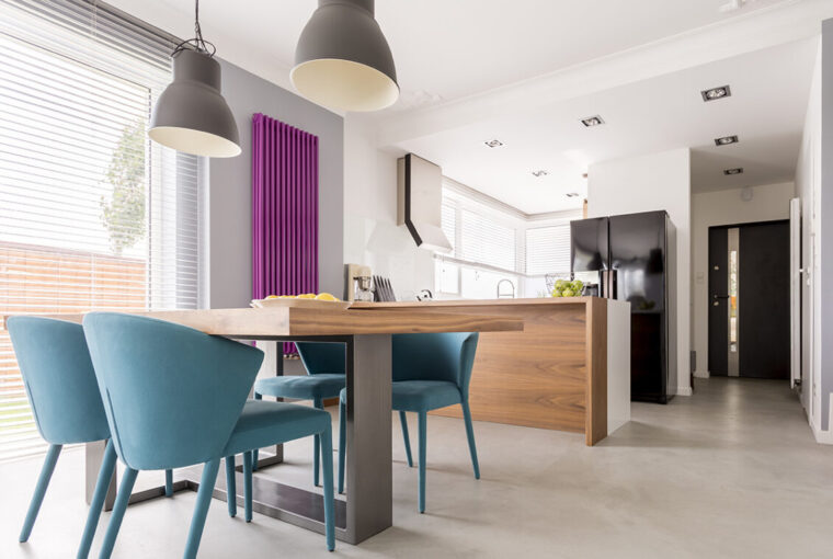 Purple radiator in contrast with white and wooden kitchen.