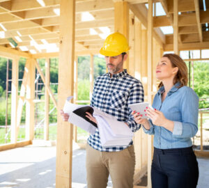 Man with hard hat and women walking around a building site. Wooden home