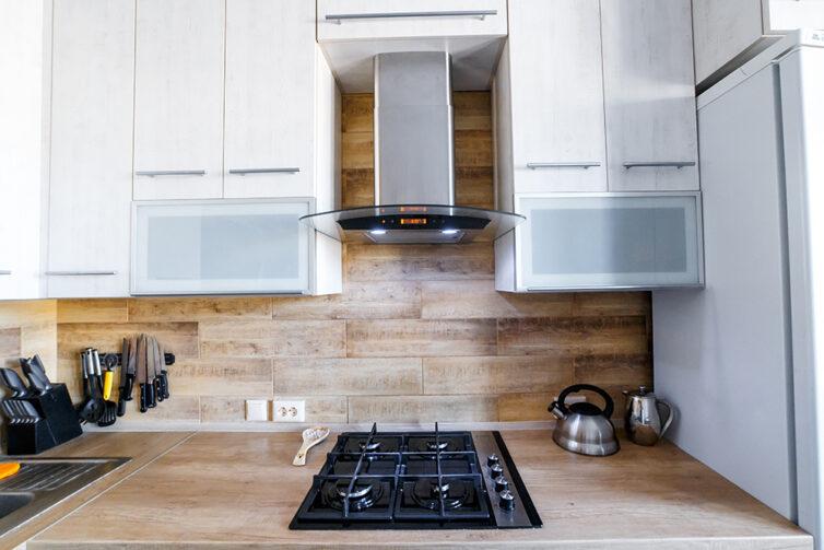 White kitchen cupboards with wooden worktops and wooden backsplash