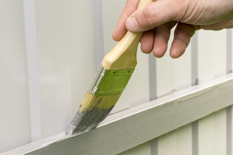 Repairing and painting wooden fence