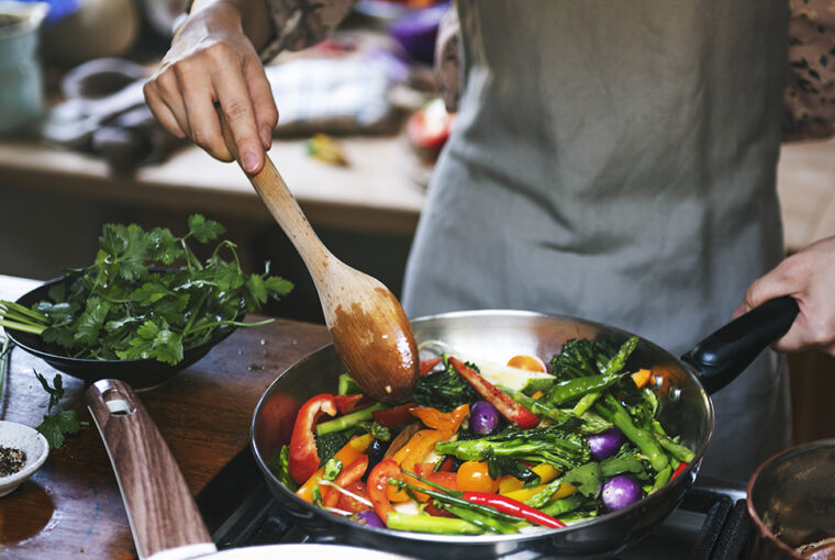 Woman cooking stir fried vegetables