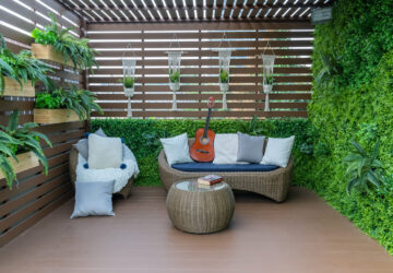 Fenced in garden with decking, plants and wicker furniture
