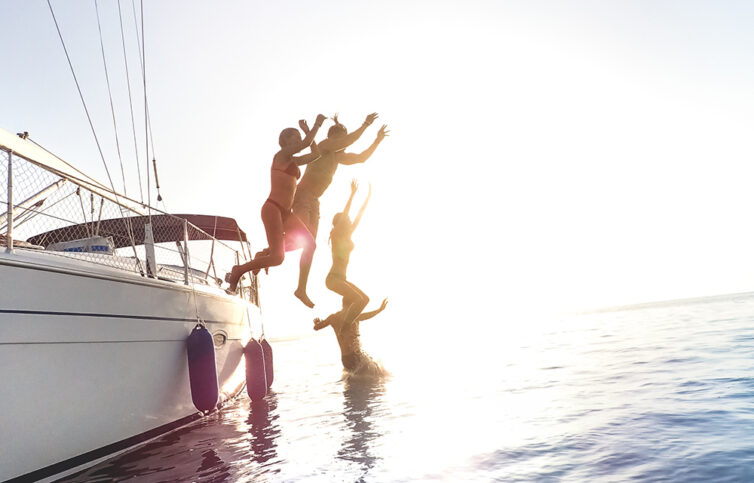 Friends jumping from sailboat on sea ocean trip