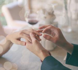 Man making marriage proposal to girlfriend at restaurant,