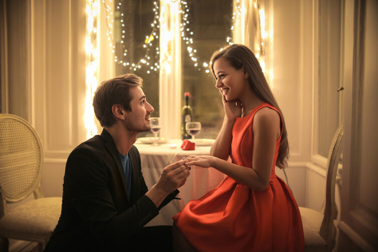 Man proposing to woman to marry him in an elegant restaurant