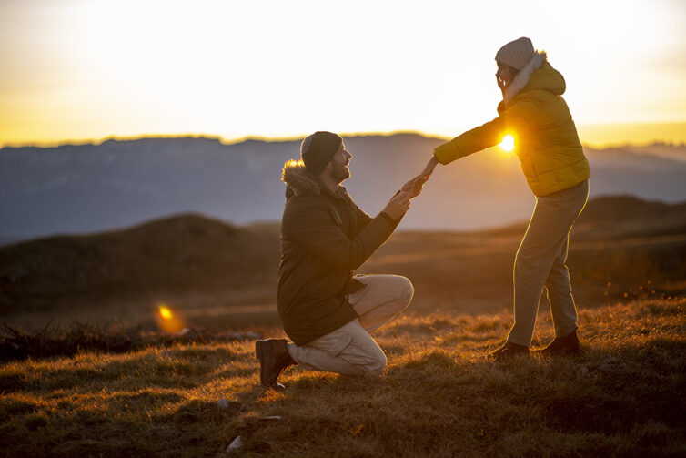 Silhouettes of a man making a marriage proposal to his girlfriend on the mountain peak at sunset.
