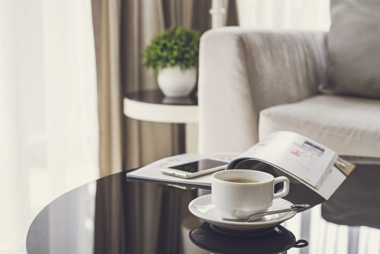Black glass coffee table with cup and saucer.