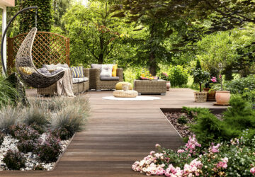 Wooden decking with wicker garden furniture. Surrounded by trees