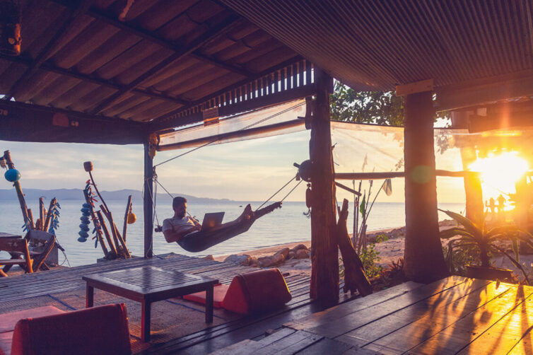 Man laying in hammock with a laptop by the beach at sunset
