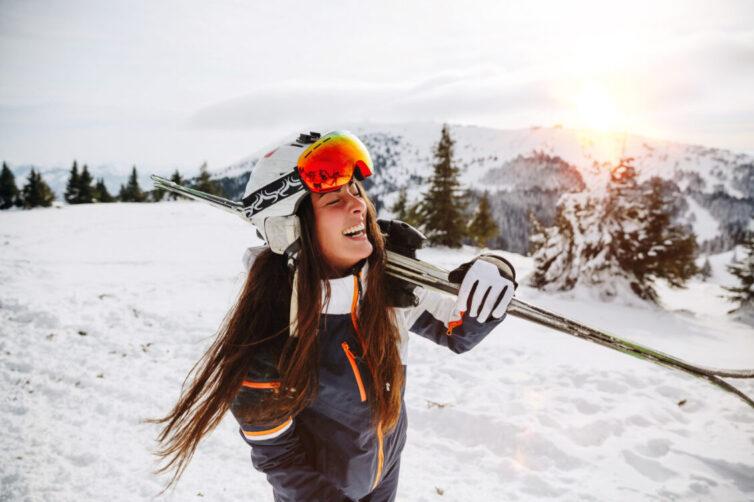 Woman carrying skis. Wearing ski googles.