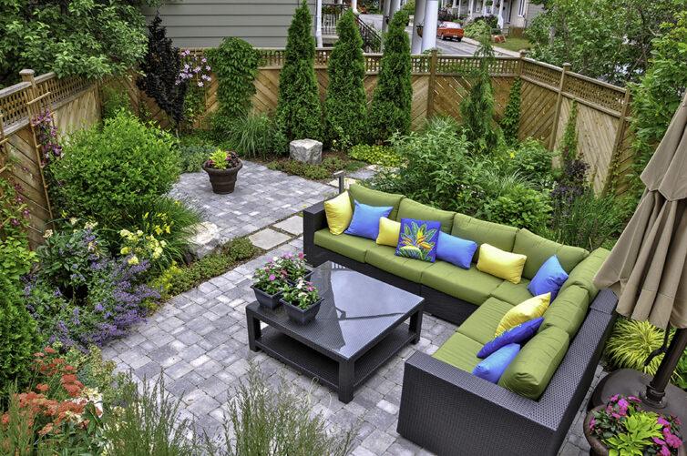 Garden with tiled patio, trees, shrubs and garden furniture
