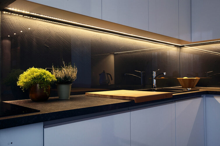 White kitchen cabinet with undercabinet LED strip lighting.