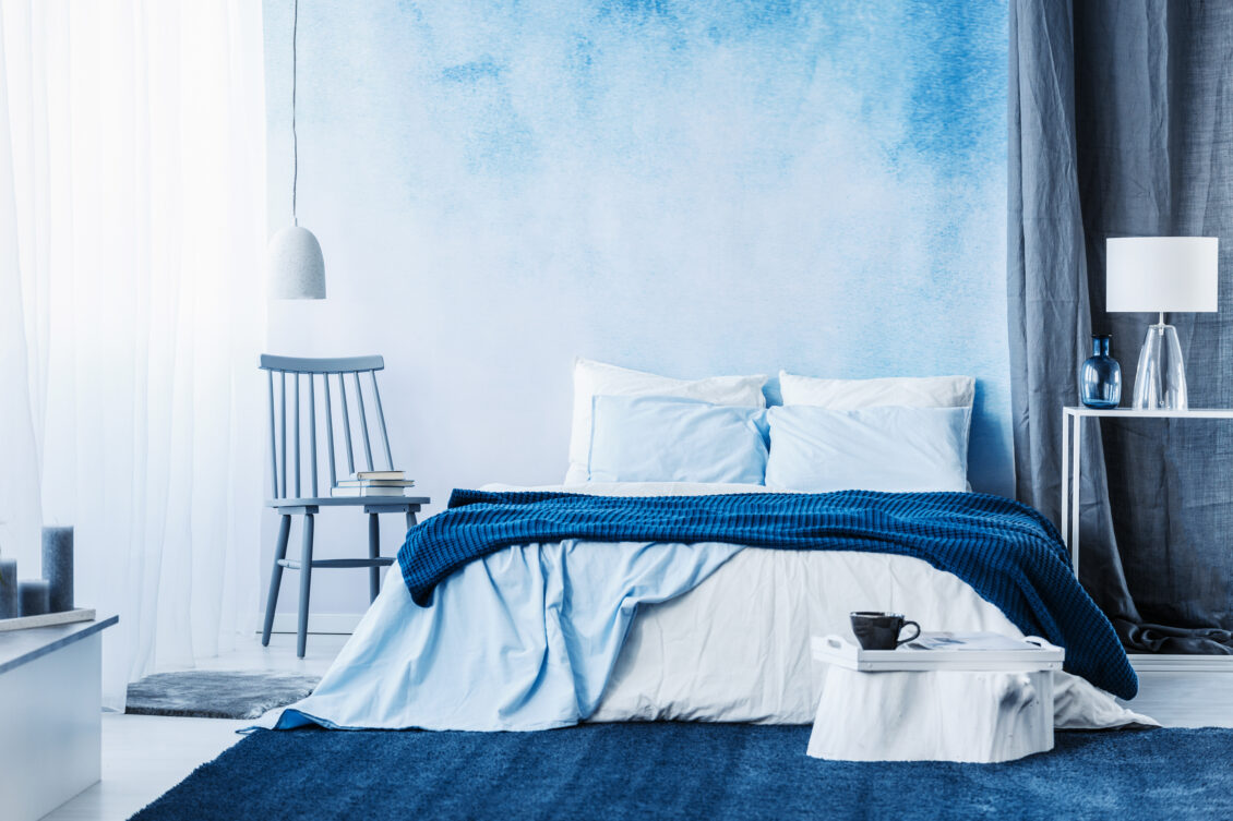 Navy blue carpet in minimal bedroom interior with blanket on bed next to a chair and under a lamp