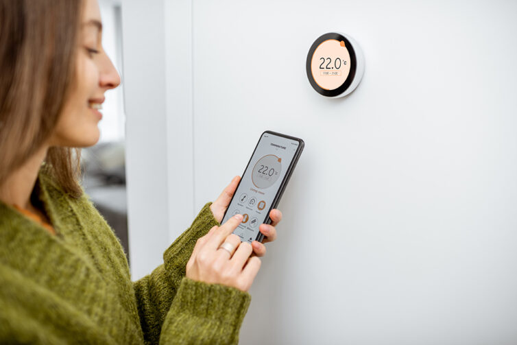 Woman regulating heating temperature with a modern wireless thermostat and smart phone.