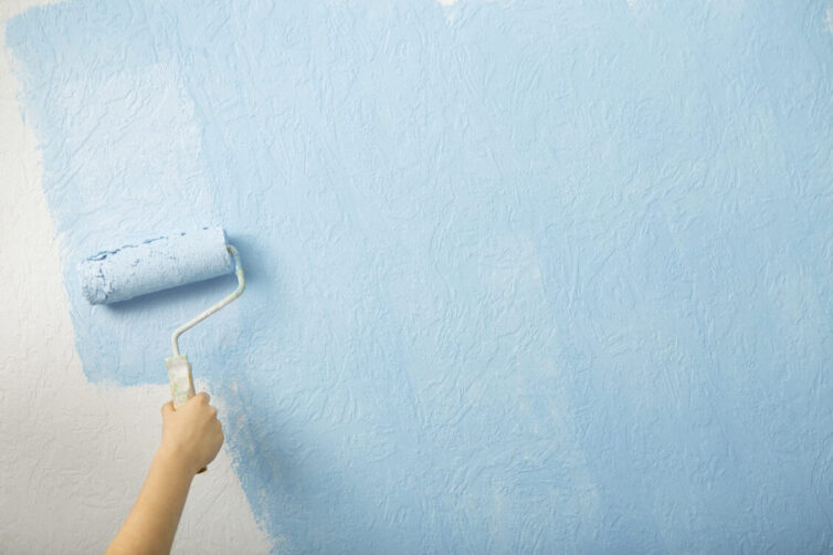 Female hand paints wall with paint roller