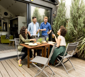 Garden party with two men and two women. Table and chairs and decking.