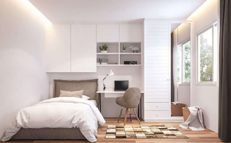 Small bedroom with single bed. Storage built in around wall and headboard of bed