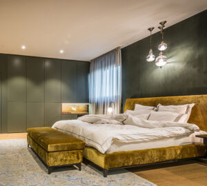 Green paintedd bedroom with gold bed. Large green built in wardrobes
