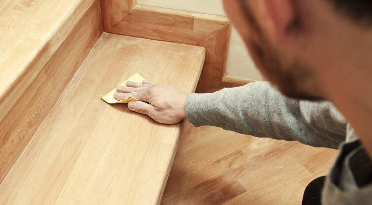 Sanding wood on staircase