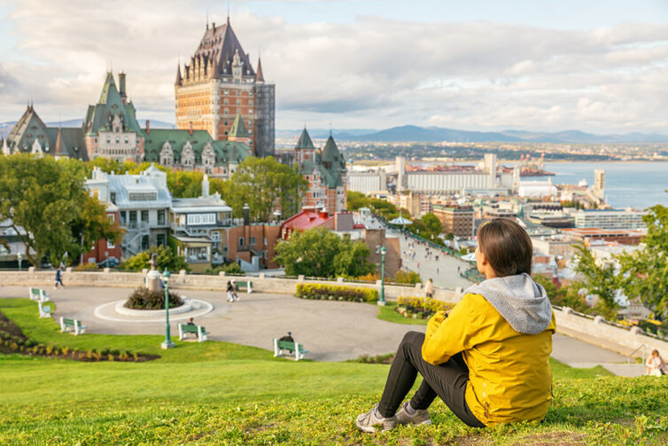 Femal student in Quebec city enjoying view of Chateau Frontenac castle and St. Lawrence river Canada