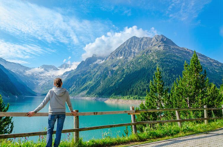 Women standing beside an azure mountain lake, Canada.