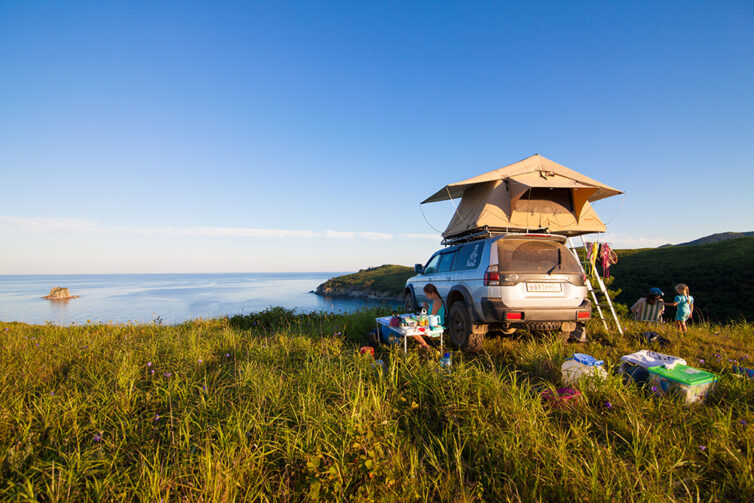 Car with roof top tent by the sea