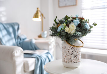 White vase with blue and white flowers placed on table in louge.