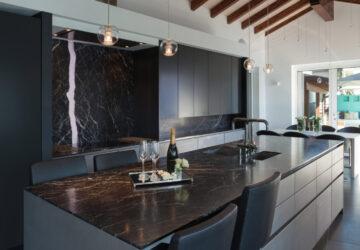 Modern stylish dark kitchen with black marble countertops